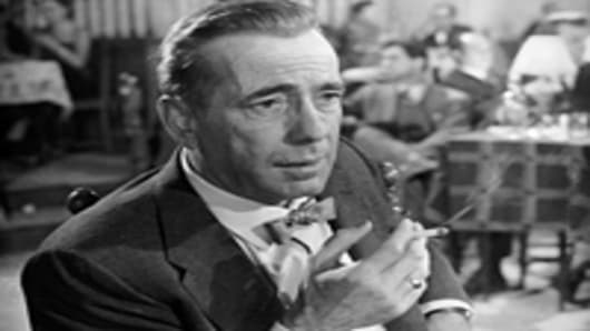 """Humphrey Bogart smoking in a cafe in a scene from """"The Barefoot Contessa."""""""