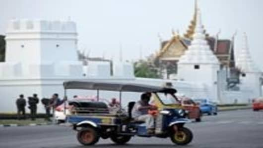 An auto rickshaw or tuk tuk drives along a street in Bangkok on January 13, 2009. The tuk-tuk, so-called because of the noise it makes when it starts, has been adopted as a Thai symbol, it actually originates in Japan. The motorized version reached Thailand in 1959, and after a few technical and aesthetic modifications, it became the colourful, open-air vehicle seen careering across Thailand today.