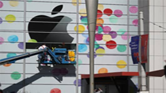 Workers apply the Apple logo the outside of the Yerba Buena Center for the Arts .