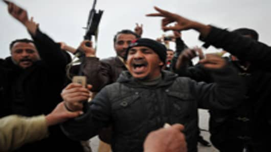 Libyans at the rebel-held eastern town of Brega celebrate after rumor spread that their fighters took over the town of Ras Lanuf from pro-Kadhafi forces during battles.