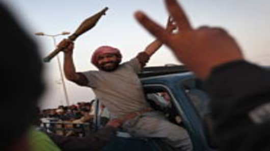 A rebel fighter greets a crowd of comrades while heading towards the frontline in Ajdabiya, Libya.