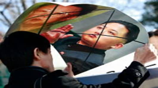North Korean defectors hold defaced posters of North Korea leader Kim Jong-Il and his son Jong-un as they participate in a anti-North Korea protest in front of the South Korean Defense Ministry on November 29, 2010 in Seoul, South Korea. Tensions between the two Koreas remain high following an artillery exchange on the disputed island of Yeonpyeong on November 24.