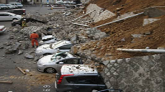 Vehicles are crushed by a collapsed wall at a carpark in Mito city