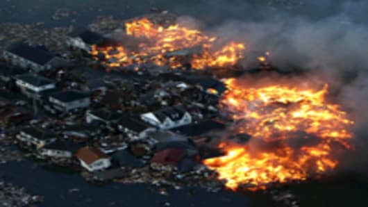 Homes in flame after being hit by a tsunami at Natori city in Miyagi