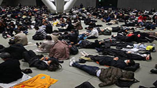 Stranded commuters sit the Tokyo International Forum