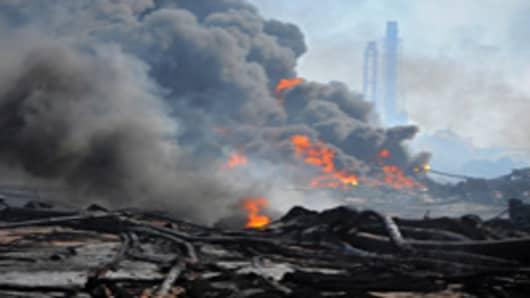 Smoke billows from fires raging at the port in Tagajo, Miyagi
