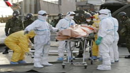 A person who is believed to be have been contaminated with radiation is carried to ambulance