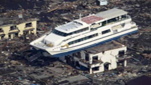 A pleasure boat sits on top of a building amid a sea of debris in Otsuchi