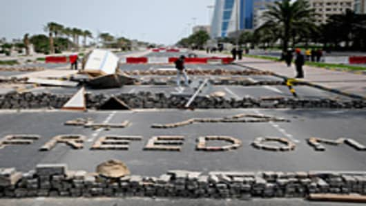 Bahraini anti-government protesters stand close to makeshift roadblocks in Manama.