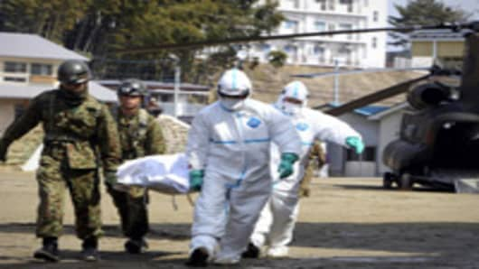 A person, who is believed to be have been contaminated with radiation, in a white bag is carried by soldiers at a radiation treatment centre in Nihonmatsu city in Fukushima prefecture on March 13, 2011.