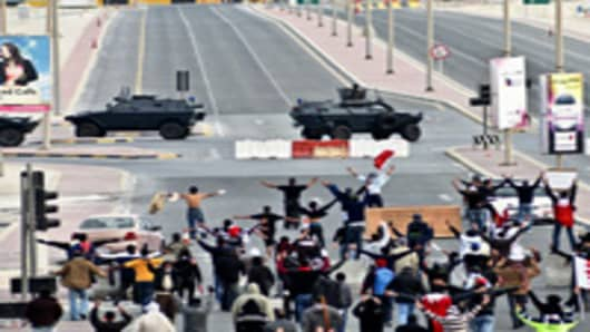 Anti-government protestors open their arms in front of military vehicles near Pearl Square in Bahraini capital Manama, on March 16, 2011, after Bahraini police killed at least two protesters and wounded dozens more as they assaulted a peaceful protest camp in the capital's Pearl Square, an opposition party official said. AFP PHOTO/STR (Photo credit should read -/AFP/Getty Images)