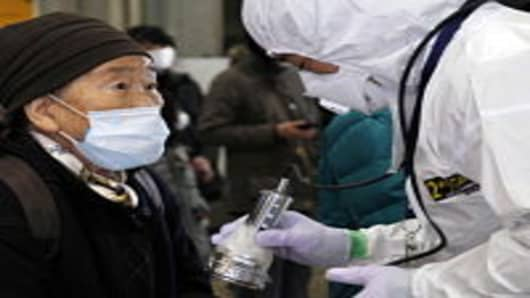 An official in a full radiation protection suit scans an evacuated elderly woman with a geiger counter to check radiation levels in Koriyama city in Fukushima prefecture.