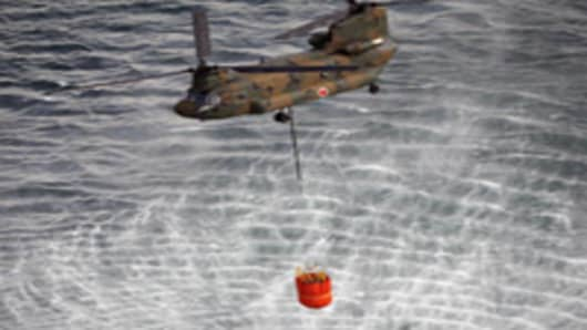 Japanese Self Defence Force's CH-47 Chinook helicopter holding more than seven tons water each with large buckets from the sea