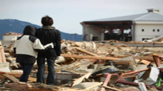 A man and his sister stand before their broken house, destroyed by the tsunami at Rikuzentakata in Iwate prefecture on March 17, 2011.