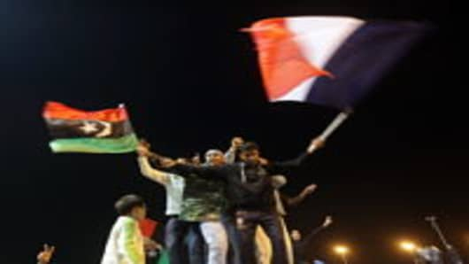 Libyans wave the flag of the Kingdom of Libya and the French tricolor as they celebrate in Benghazi.