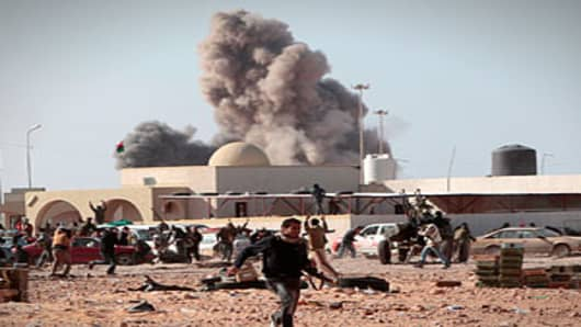 Anti-Gaddafi rebel runs away as smoke rises following an air strike by Libyan warplanes.