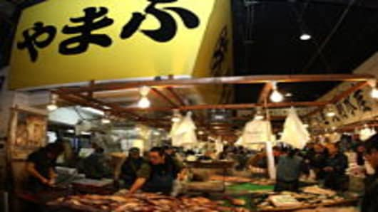 Customers buy fish on sale at a stall during the new year's first auction at the Tsukiji fish market on January 5, 2010 in Tokyo, Japan. The market handles approx 2,888 tons of fish a day generating over 2.8 billion yen.