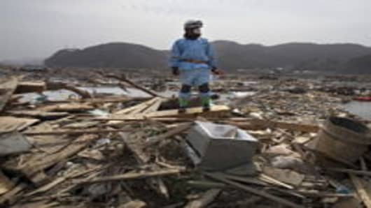 A rescue worker stands atop rubble during a body recovery mission March 20, 2011 in Ofunato, Japan. More than a week after the magnitude 9.0 earthquake and tsunami struck Japan, the death toll has risen to over 8,000 with thousands more still missing. Presently the country is struggling to contain a potential nuclear meltdown after a nuclear plant was seriously damaged by the quake.