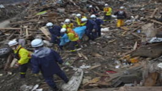 Rescue workers carry a body from the rubble in Rikuzentakata, Japan.