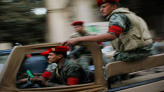 Egyptian security forces race through the streets near the scene Interior Ministry building that caught fire March 22, 2011 in downtown Cairo, Egypt.