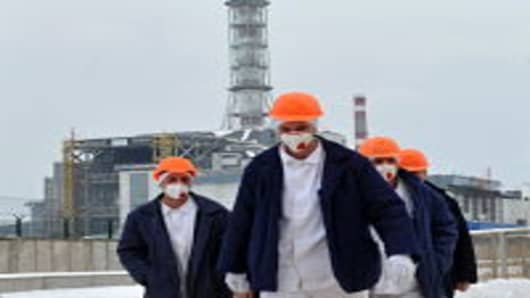 Employees of the Chernobyl Nuclear Power Plant walk outside of the destroyed 4th block of the plant on February 24, 2011 ahead of the 25th anniversary of the meltdown of reactor number four due to be marked on April 26, 2011. Ukraine said early this year it will lift restrictions on tourism around the Chernobyl nuclear power plant, formally opening the scene of the world's worst nuclear accident to visitors. Chernobyl's number-four reactor, in what was then the Soviet Union and now Ukraine, expl