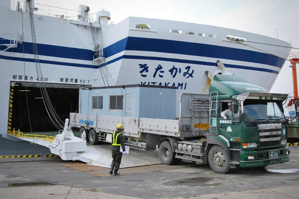 A temporary house for evacuees is transported out from a large ferry boat on the back of a flatbed truck at the port in Sendai in Miyagi prefecture on March 25, 2011.