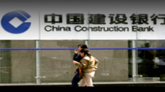 Two Chinese girls make their to the China Construction Bank head office in Beijing 28 October 2005. China Construction Bank (CCB) met a muted response from investors in its debut on the Hong Kong Stock Exchange after making the world's biggest share offer in four years.