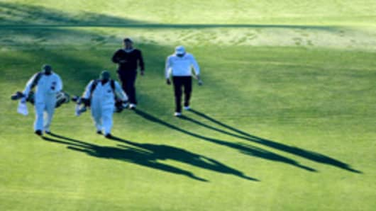 Adam Scott of Australia and Nick Watney (R) walk with their caddies on the first hole during the first round of the 2011 Masters Tournament at Augusta National Golf Club on April 7, 2011 in Augusta, Georgia.