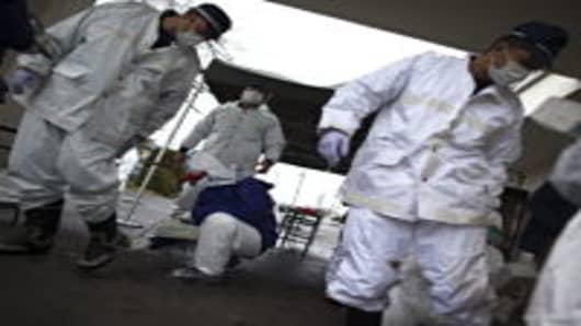 Japanese policemen wearing a protective suits undergo testing for possible nuclear radiation at screening center about 35 kilometers away from Fukushima Nuclear Power Plant as they finish their duty inside exclusion zone in Minamisoma, Fukushima Prefecture, Japan.