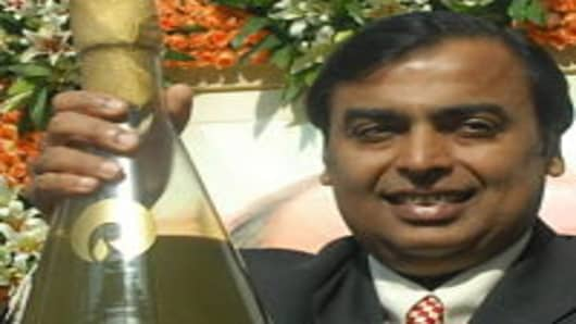 Reliance Industries chairman Mukesh Ambani holds a glass container filled with crude oil extracted from the D6 block of Krishna Godavari (KG) basin in September 2008. Ambani is India's richest man.