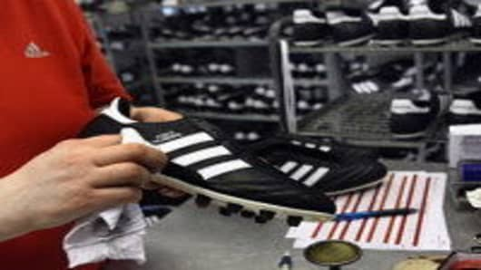 An employee examines football boots at the final check of the factory of German sporting-goods maker Adidas AG in Scheinfeld, Germany.