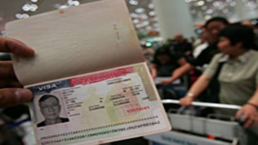 A U.S. visa is shown by a tourist as the first group of Chinese tourists set out to visit US at the Beijing Capital International Airport on June 17, 2008 in Beijing, China.