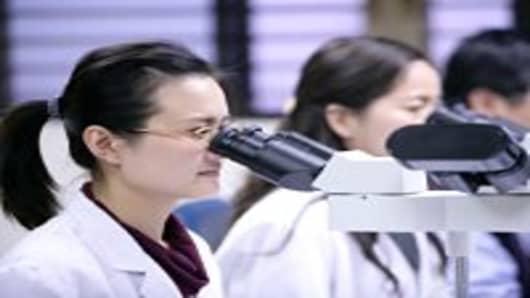 Three laboratory technicians using microscope