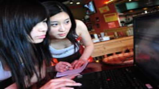 Chinese ladies accessing wireless internet at a Beijing restaurant.