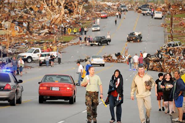 A massive tornado that tore a 6-mile (10-kilometer) path across southwestern Missouri killed at least 89 people as it slammed into the city of Joplin. Here, residents of Joplin walk down the street after the May 22 tornado.