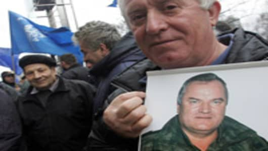 BELGRADE, SERBIA - FEBRUARY 24: A Serbian Radical party supporter holds a photo of war crimes suspect Ratko Mladic at a rally in Belgrade February 24, 2006. A Serbian ultranationalist party on Thursday urged fugitive Bosnian Serb general Ratko Mladic not to surrender to the UN warcrimes court, despite mounting pressure on Belgrade to hand over one of the most wanted suspects of the Balkan wars in 1990s. (Photo by Milos Bicanski/Getty Images)