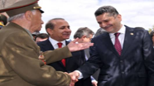 Armenian Prime Minister Tigran Sarkisian (R) shakes hands with a World War II veteran on May 9, 2011 as Parliament Speaker Hovik Abrahamian (C) listens during Victory Day celebrations in Yerevan, marking the 66th anniversary of the end of World War II.