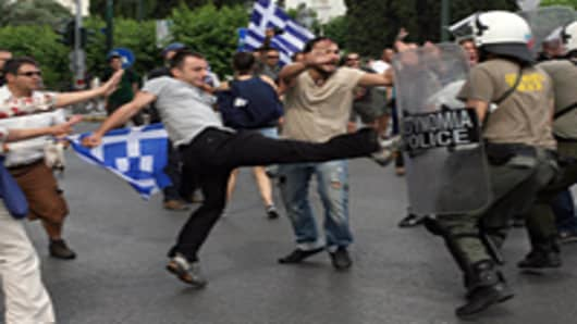 A protester kicks a riot police officer during a general strike against government austerity plans, in Athens.