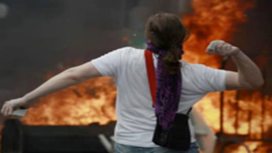 Protester throws a stone during demonstration at anti-austerity rally.