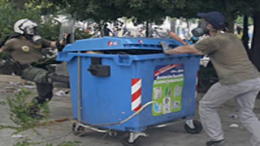 Riot police and protester clash around recycle bin during demonstration at anti-austerity rally.