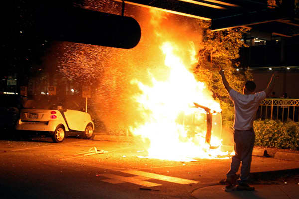 A person walks in front of a burning vehicle on June 15, 2011 in Vancouver, Canada. Vancouver broke out in riots after their hockey team the Vancouver Canucks lost in Game Seven of the Stanley Cup Finals.