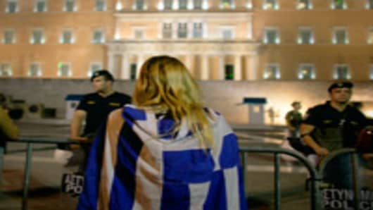 A protester wears a national flag near to the Syntagma square in front of the Greek Parliament.
