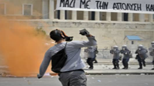A protestor throws a stone to riot police in front of the Greek Parliament.