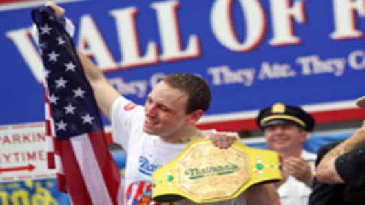 "NEW YORK - JULY 4: Joey Chestnut (L) of San Jose, California holds up the American flag and his champion belt after defeating Takeru Kobayashi of Nagano, Japan and Patrick ""deep dish"" Bertoletti in the Nathan's Famous Fourth of July hot dog eating contest on July 4, 2009 in Coney Island in the Brooklyn borough of New York City. Chestnut defeated Kobayashi with eating 68 to his 64.5 hotdogs. Kobayashi won six previous competitions before tying last year with Chestnut. (Photo by Yana Paskova/Getty"