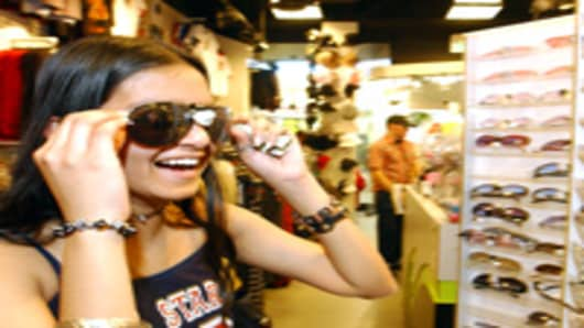 Fourteen-year-old Khine Thwin tries on sunglasses at a Hot Topic retail store at the Serramonte Mall in Daly City, CA.