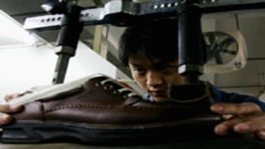 A man operates a shoe production machine at a leather shoe factory on March 3, 2006 in Wenzhou of Zhejiang Province, China. Wenzhou is one of the major shoe production bases of China, with more than 4,500 shoe factories and an annual output of 600,000 pairs. The European Union (EU) will impose import duties as high as 20 percent on some leather shoes from China and Vietnam starting in April. Over 70 batches of Chinese shoes have been stockpiled in Northeast China's Dalian Port since the middle o