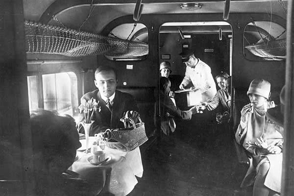 Sandwiches, fruit and chocolate were offered on London-to-Paris flights as early as 1919. But in 1928, Lufthansa became the first airline to serve food and drinks to its passengers. It was an especially grand experience on Lufthansa's Junkers G38 plane, where passengers sat inside a dining room found within the plane's thick wings.At left, passengers on board the Lufthansa Berlin-Vienna Air Express service enjoy a meal.Patricia Friend, president of the flight attendants' union AFA-CWA, said in a
