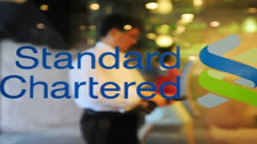 A man walks past a logo of Standard Chartered bank at the headquarters of SC First Bank in Seoul on June 27, 2011.