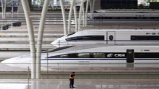 A member of the security staff stands on the platform next CRH380A train, foreground, used on the Beijing-Shanghai high-speed line, at the Hongqiao Station in Shanghai, China.