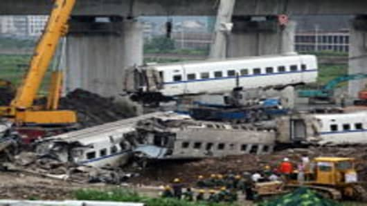 The wreckage of a carriage is lifted from the accident scene of the crash caused by the earlier collision of two trains on July 24, 2011 in Wenzhou, Zhejiang Province of China. The accident occurred on the evening of July 23 when the D301 train, travelling from Beijing to Fuzhou, collided with the D3115 train, travelling from Hangzhou to Fuzhou, which had stalled on the line after a suspected lightening strike. The first four coaches of D301 fell off the viaduct while the 15th and 16th coaches o